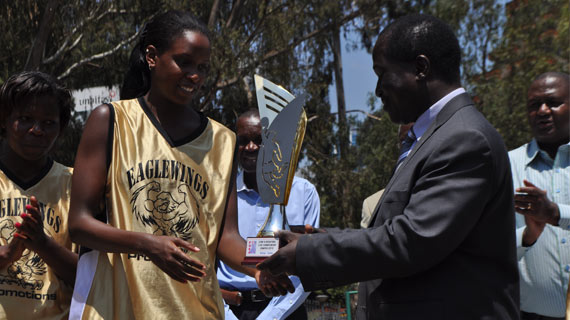 Silalei Shani presents winners trophy to commissioner Oluoch
